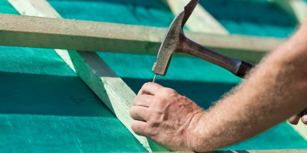 Roofer,Hammering,A,Nail,Into,The,New,Roof,Beams